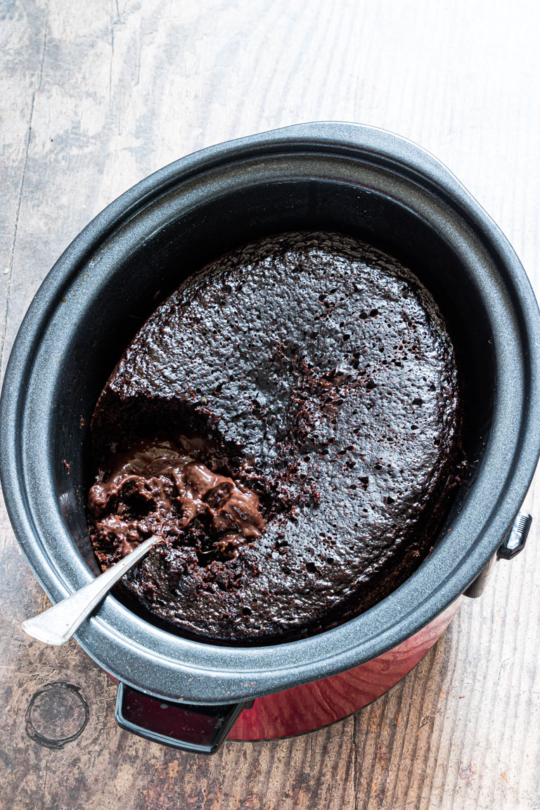 the completed crock pot lava cake inside the crockpot with a serving removed