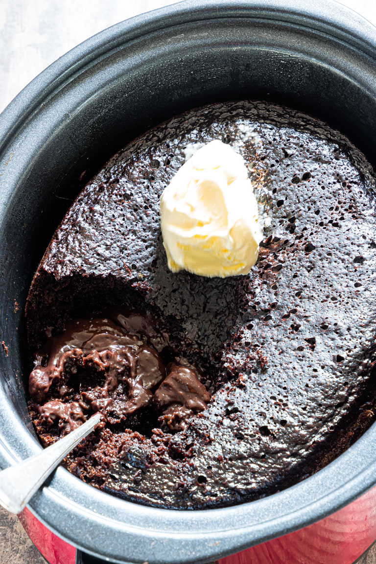 the finished crockpot lava cake inside the slow cooker with a scoop of ice cream on top and a serving spoon stuck inside