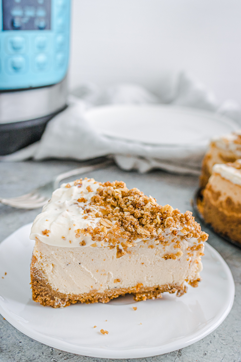 one slice of cheescake on a white plate and set in front of the Instant Pot
