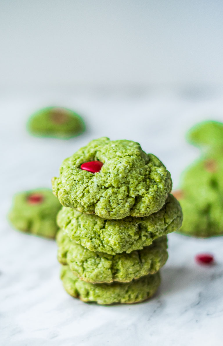 four grinch cookies stacked on top of one another