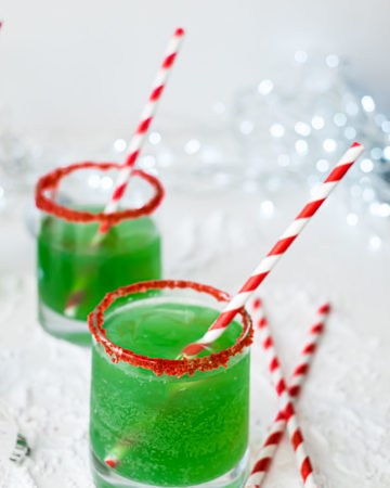 two glasses of Grinch punch served with red striped straws