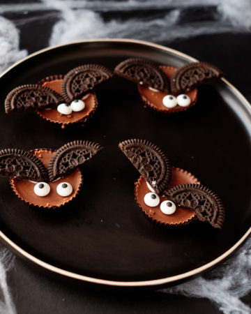four of the completed bat halloween cookies served on a plate