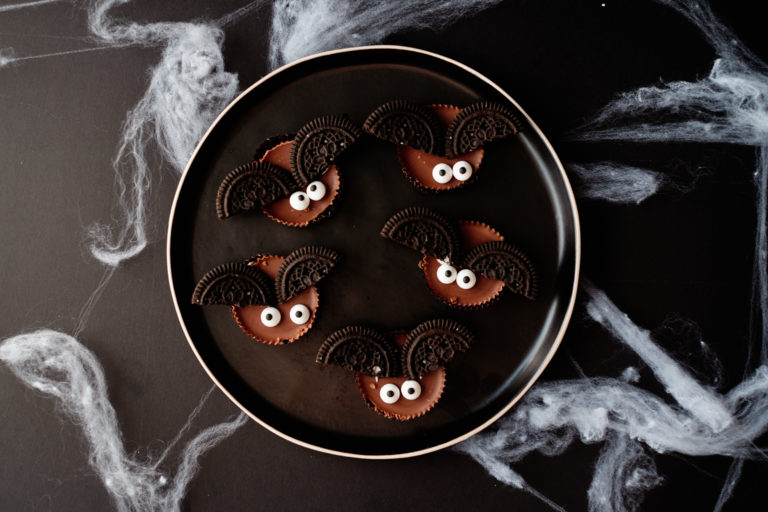 five bat cookies served on a dark colored plate