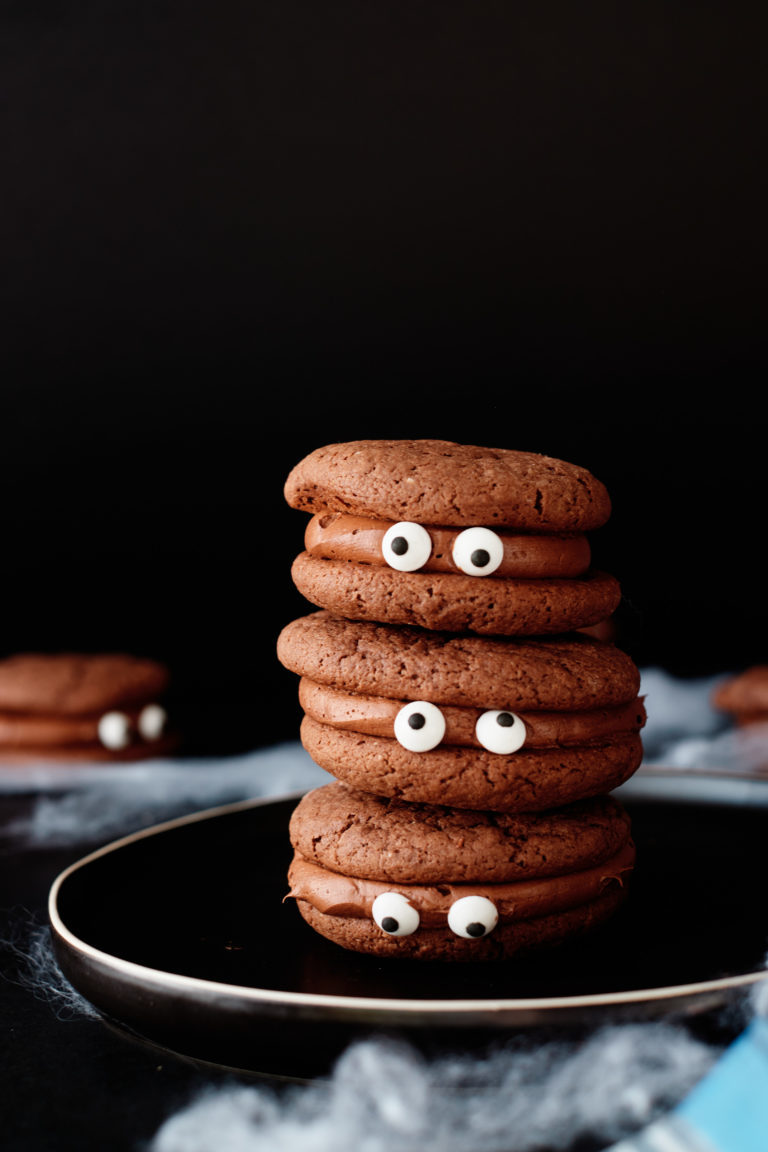 three completed monster eye cookies stacked and served on a dark colored plate