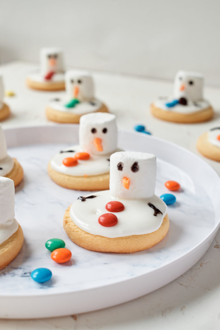an assortment of snowman cookies on a white plate