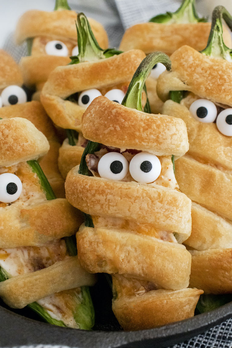 close up view of a stack of mummy jalapeno poppers