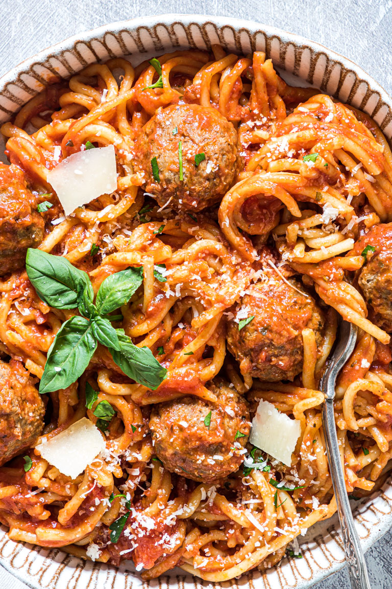 the completed spaghetti and meatballs served on a plate and garnished with fresh basil