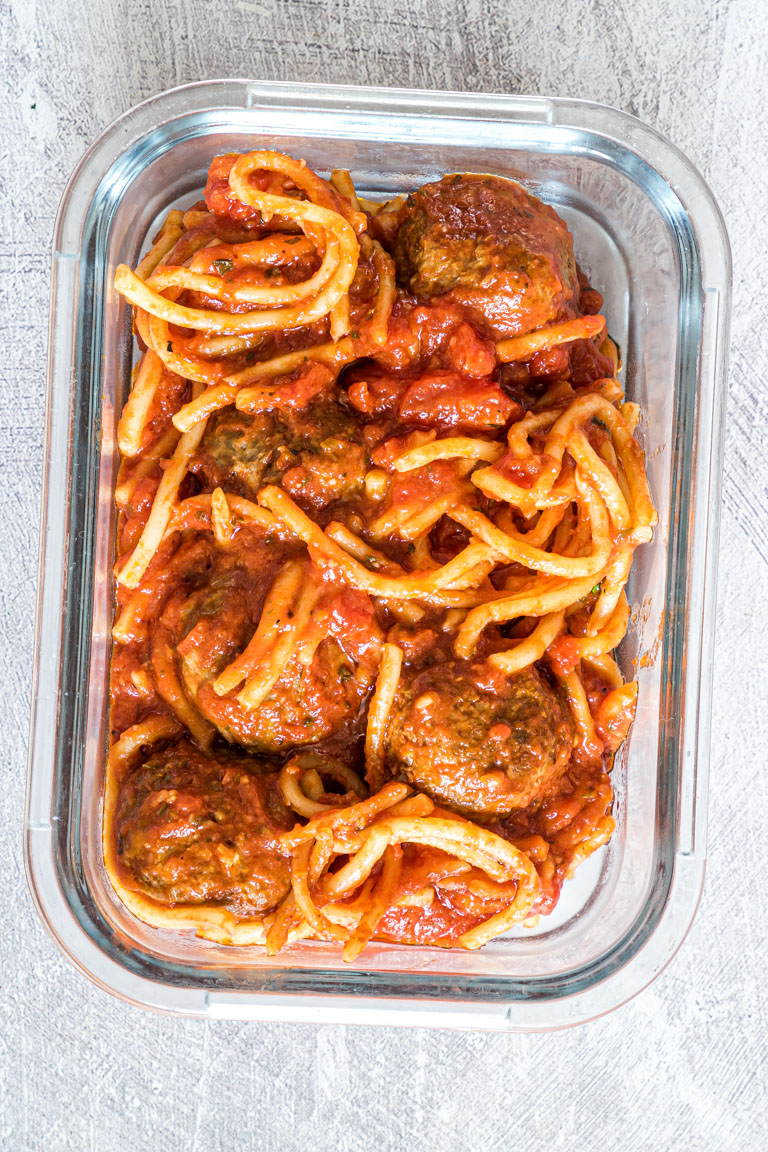 some spaghetti and meatballs and sauce in a meal prep glass container