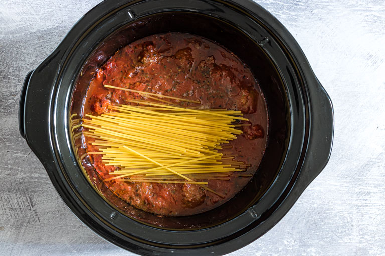 crockpot spaghetti and meatballs  - spaghetti being added into the sauce