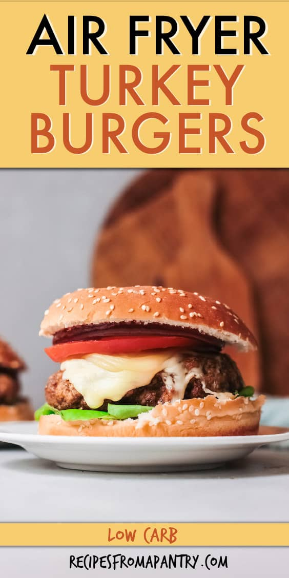 turkey burger with cheese and tomato on a plate