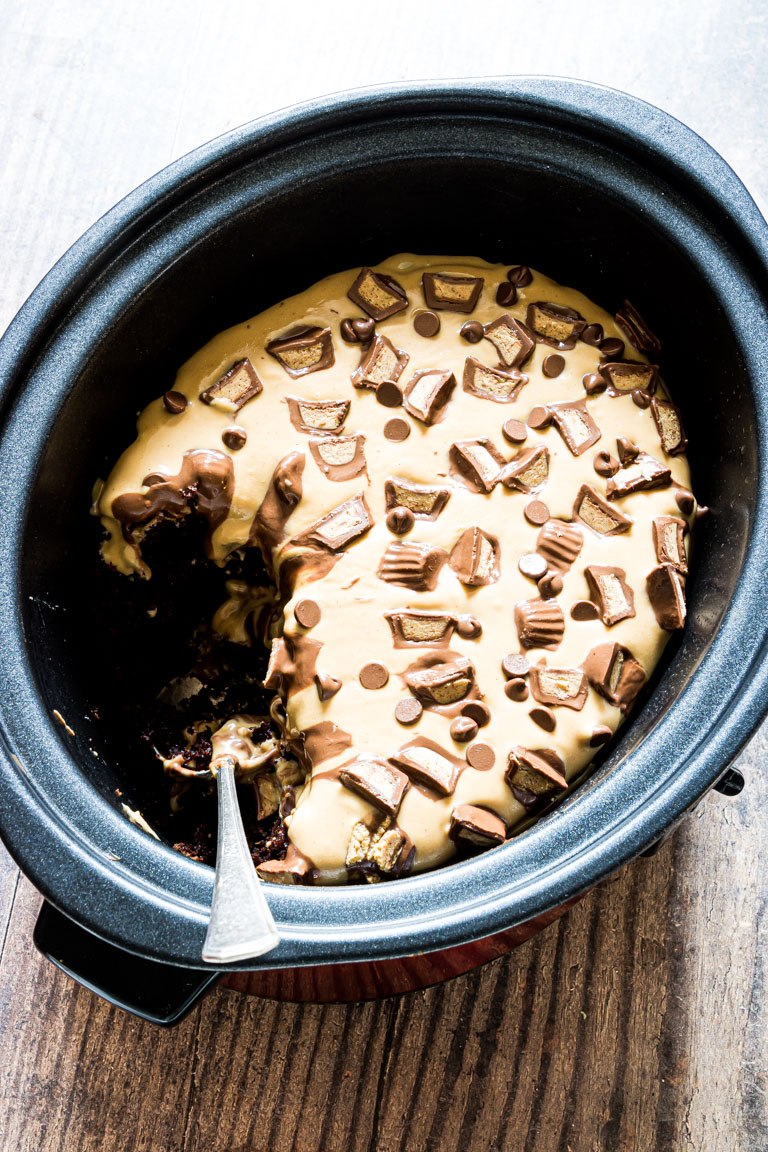 the finished crockpot peanut butter chocolate cake inside the crockpot with a serving removed
