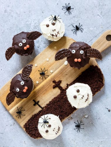 Halloween cupcakes decorated to look like bats and skulls set on a wooden cutting board painted with a graveyard scene along with plastic toy spiders