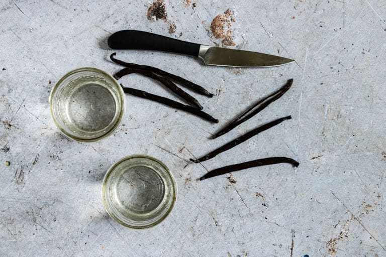 top-down view of two canning jars, vanilla beans and knife set on countertop for making Instant Pot Vanilla Extract