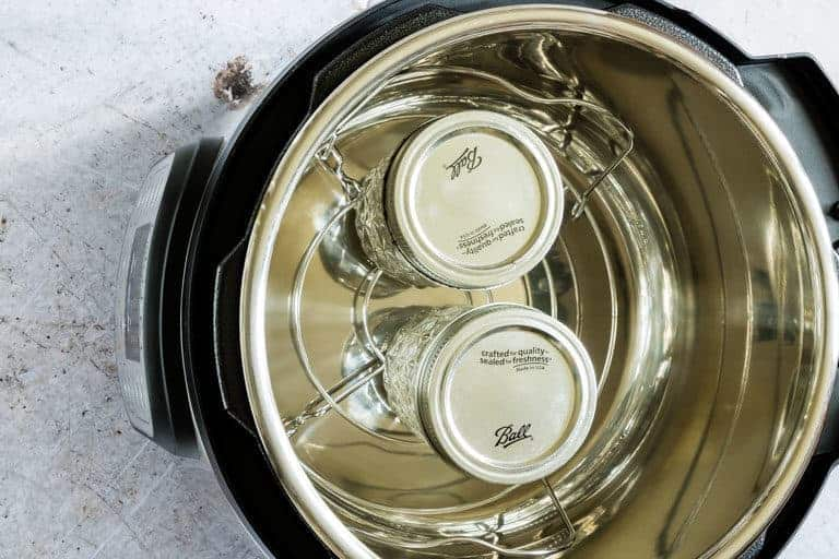 Two sealed jars of Instant Pot Vanilla Extract sitting on trivet inside the Instant Pot