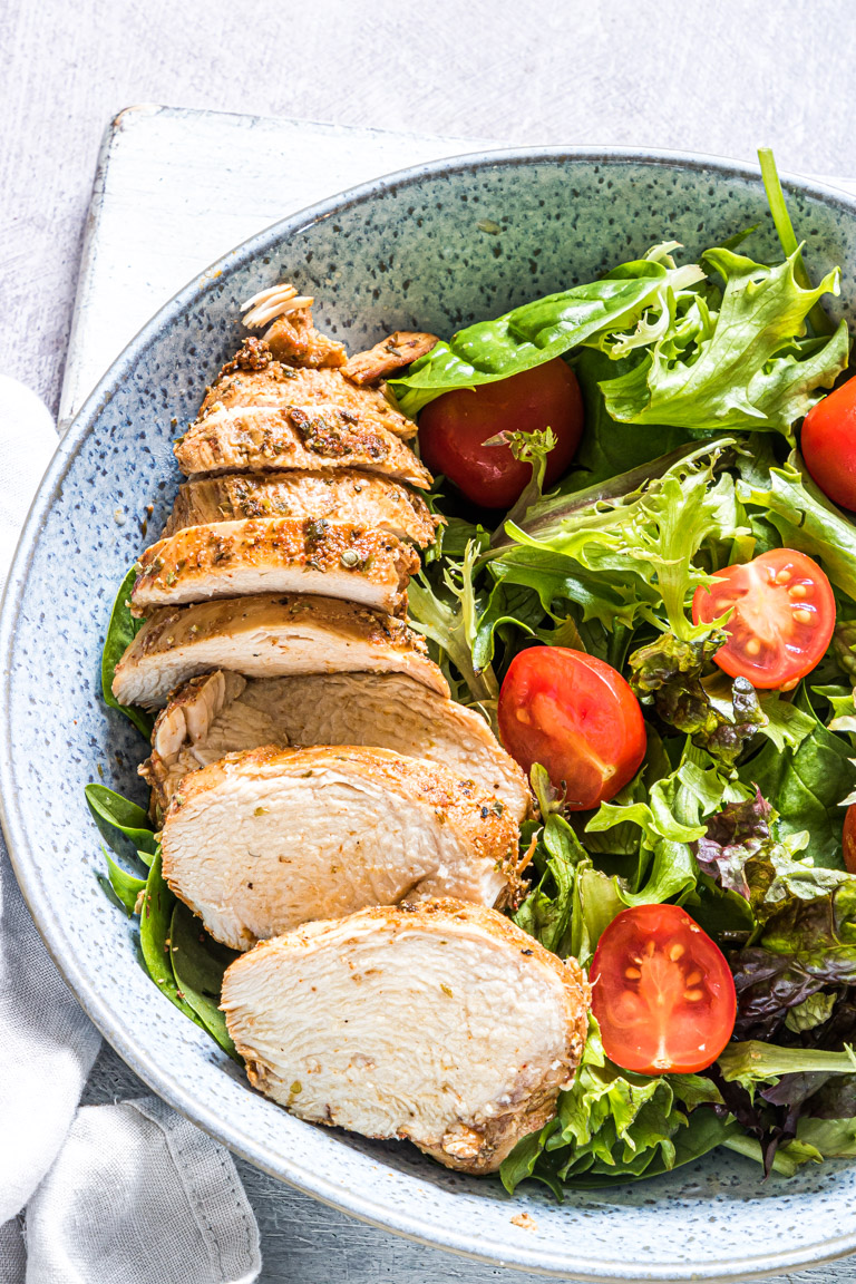 Close up of sliced chicken  breast on a salad with tomatoes and lettuce