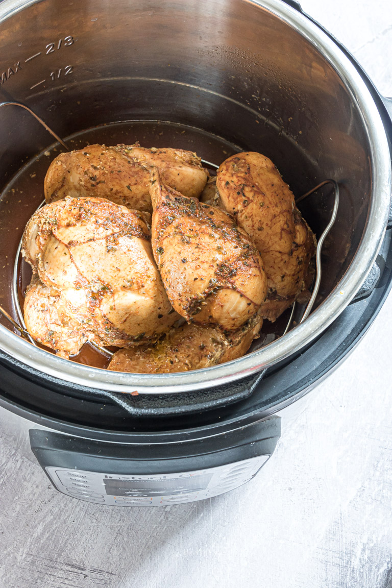 Close up of a pile of juicy chicken breasts in the instant pot on a trivet