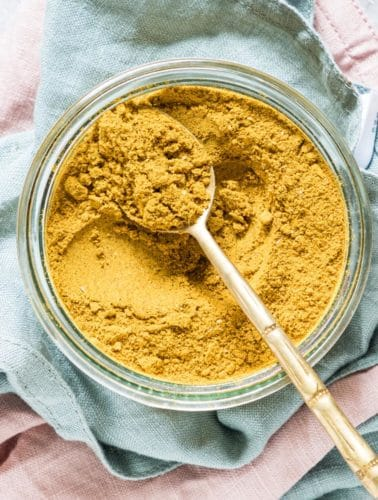 close up view of jar filled with Jamaican Curry Powder with a gold spoon
