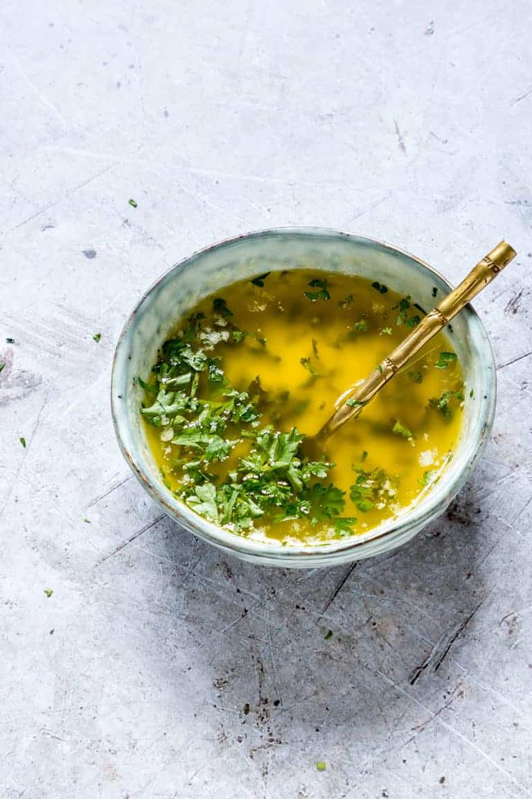 Completed Lemon Butter Sauce in a blue bowl and ready to serve with a gold-handled spoon