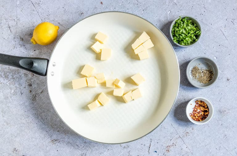 Cubed butter inside a light-coloured saucepan set next to a lemon, small bowl of chopped fresh herbs, small bowl of black pepper, and a small bowl of chilli flakes and ready to be made into Lemon Chilli Butter Sauce