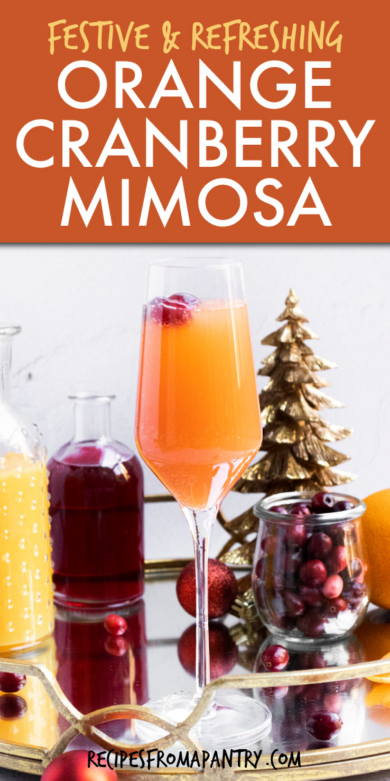 glass of cranberry mimosa with christmas decorations around it