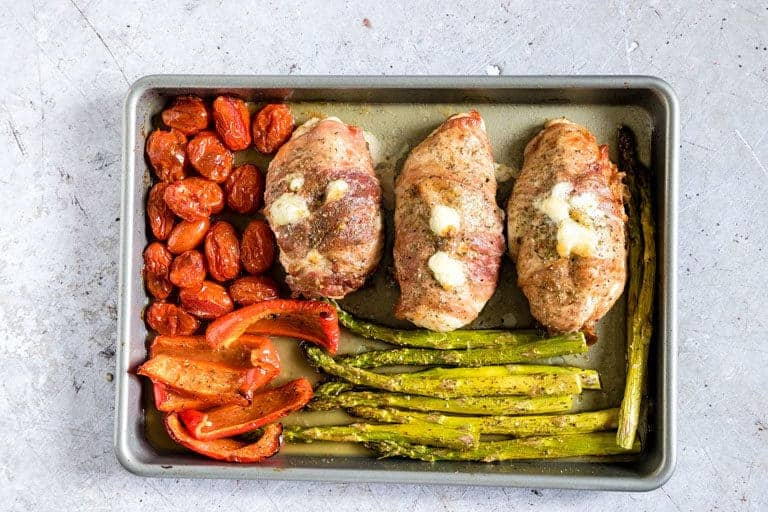 Proscuitto wrapped chicken and vegetables arranged on a baking sheet and just out of the oven