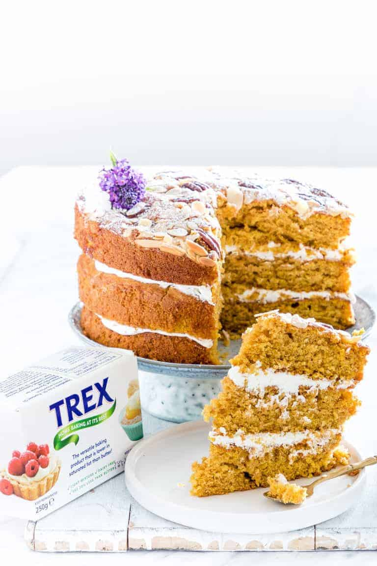 The completed Pumpkin Cake served on a white cake stand with one slice removed and set on a white dessert plate next to a package of TREX