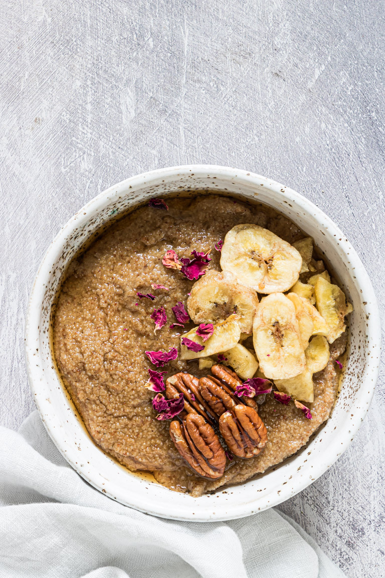 teff porridge in a bowl and garnished with sliced banana, walnuts and herbs