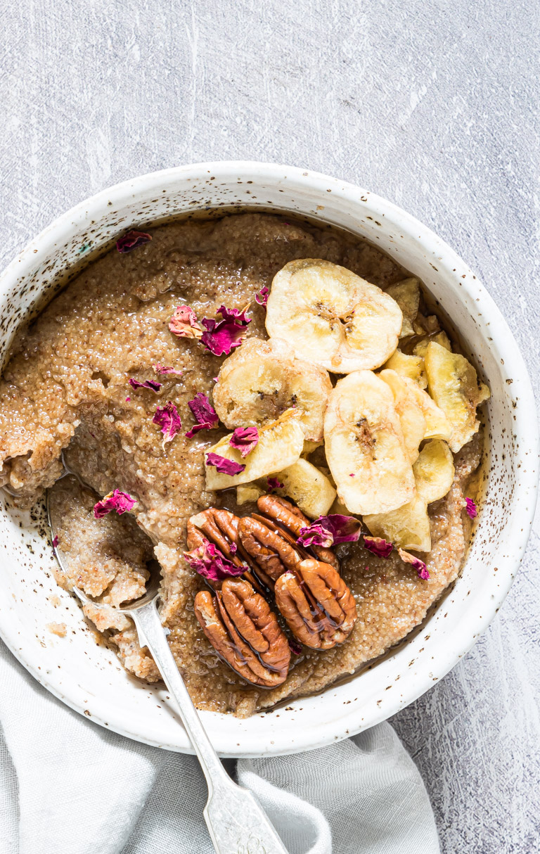 the finished teff porridge topped with banana and nuts and served with a spoon and cloth napkin