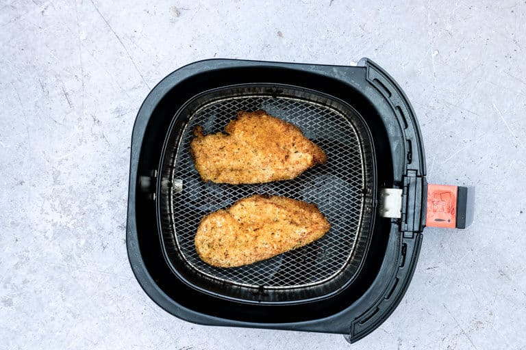 The finished crispy air fryer chicken breasts inside the air fryer basket and ready to serve
