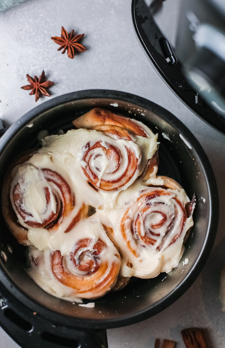 4 of the completed air fryer cinnamon rolls with bacon topped with frosting