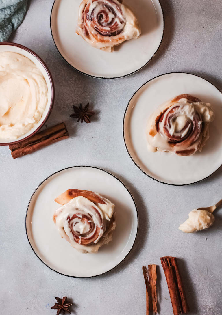 top down view of two bacon cinnamon rolls served extra frosting on a spoon
