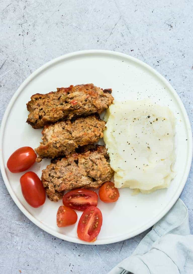sliced air fryer meatloaf with mashed potatoes and tomatoes