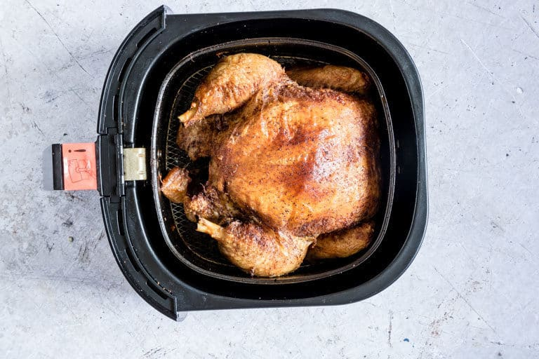 view of the finished air fryer whole chicken inside the air fryer