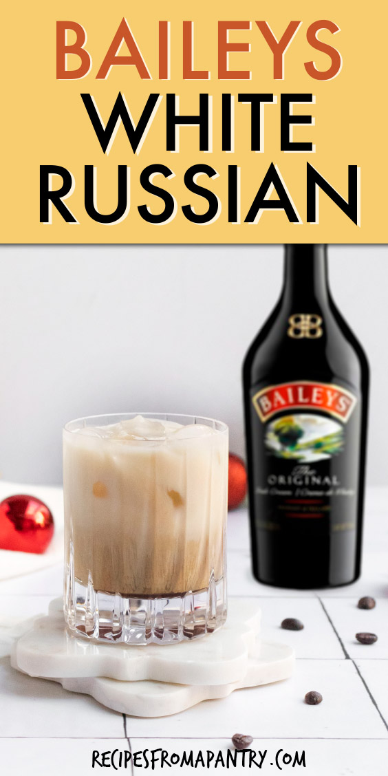 A glass of white russian cocktail on a coaster with a bottle of Baileys irish cream in the background