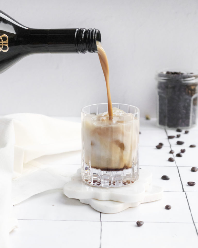 baileys being poured into a white russian cocktail