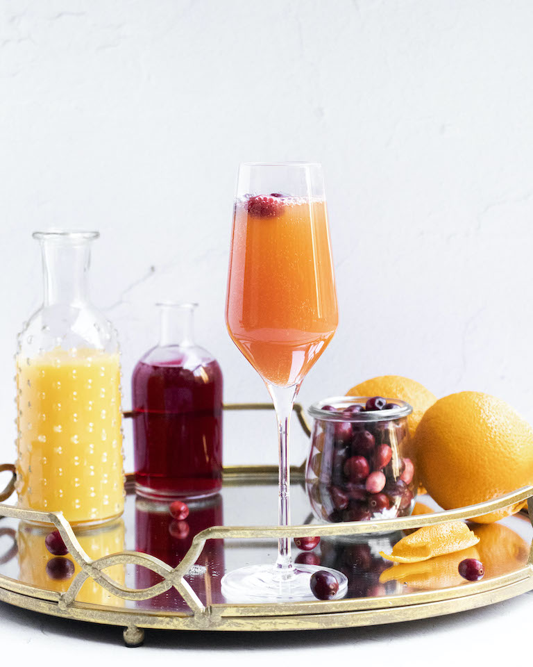 a finished cranberry mimosa on a serving try along with all of the ingredients