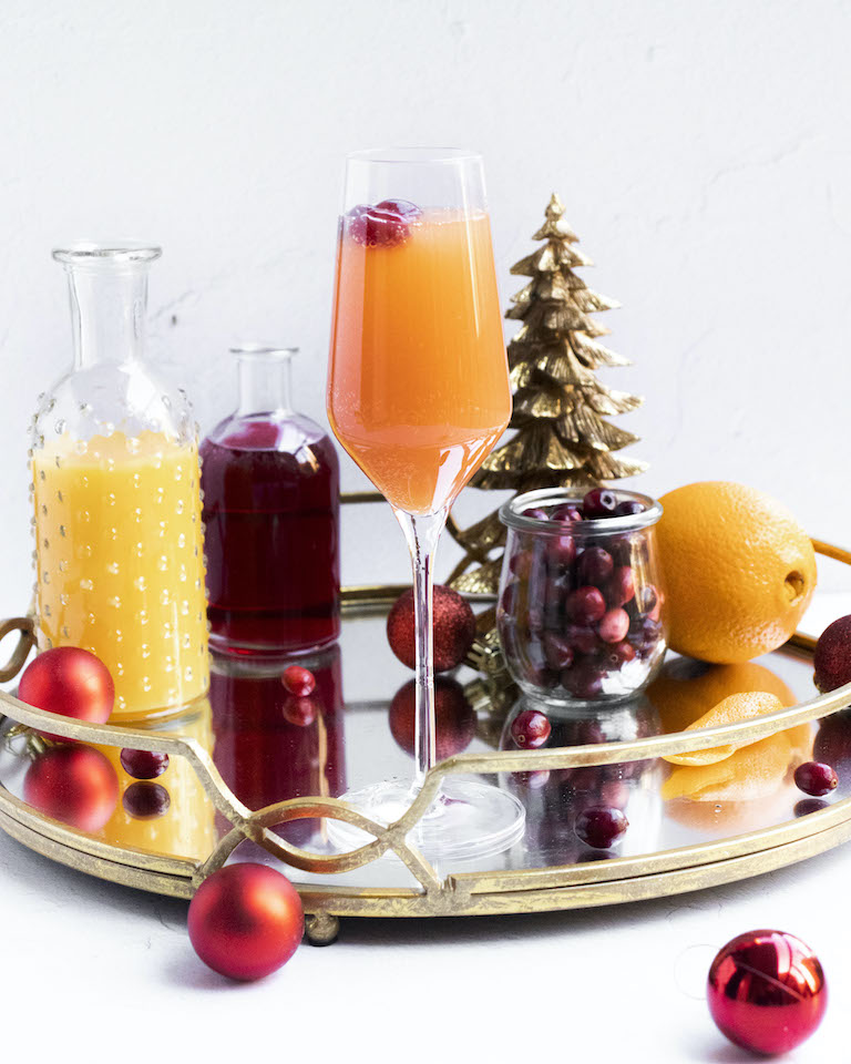 a festive cranberry mimosa on a serving tray with the ingredients and Christmas decorations