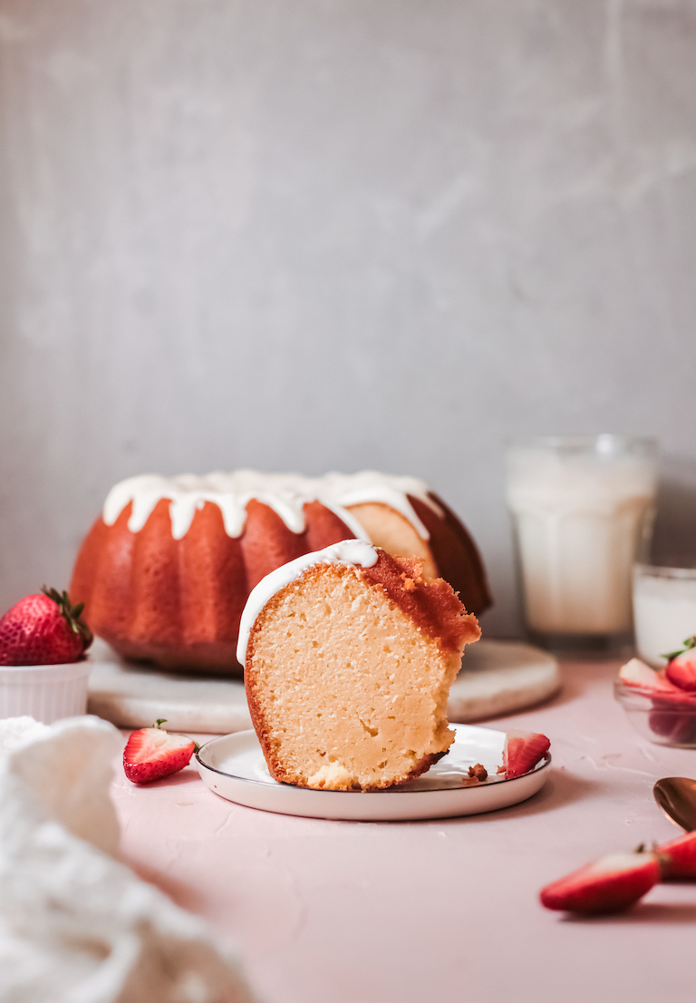 one slice of the pound cake served on a plate with strawberries with the rest of the cake in the background