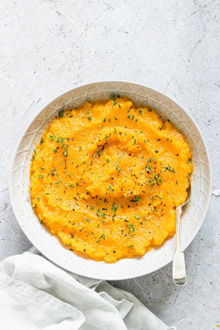 crockpot mashed butternut squash served in a white bowl and topped with herbs
