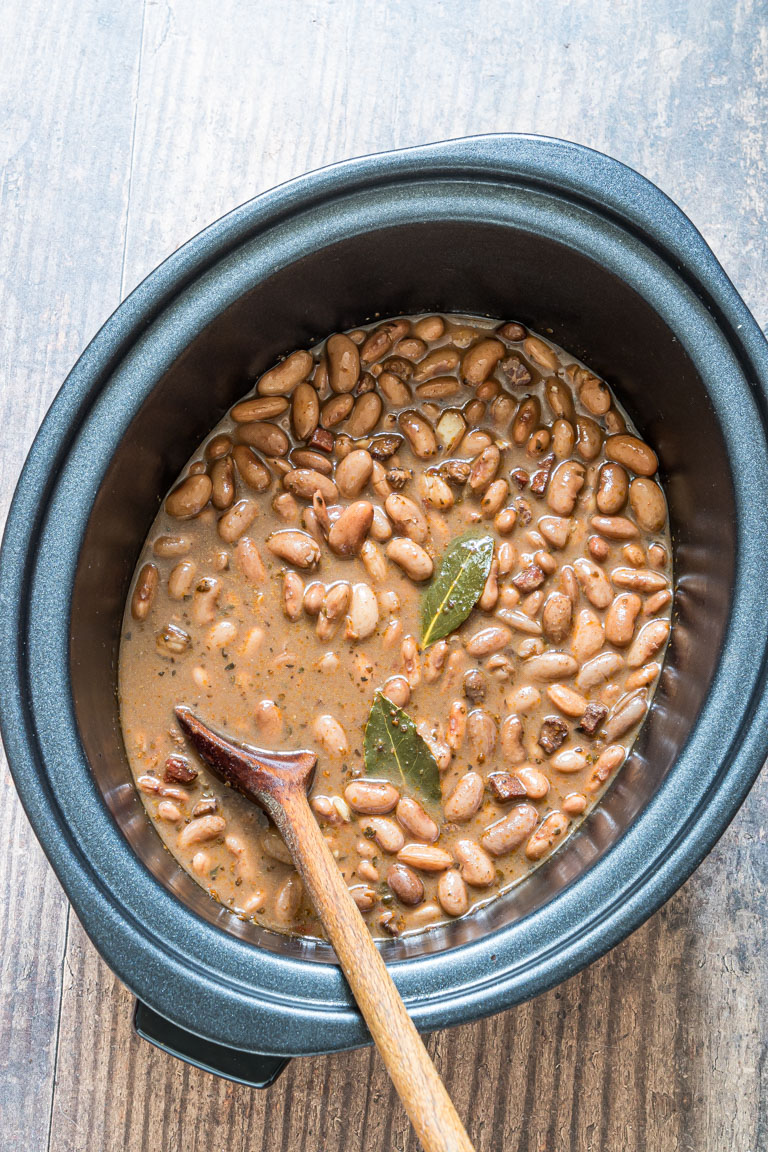 the finished pinto beans being stirred inside the crock pot