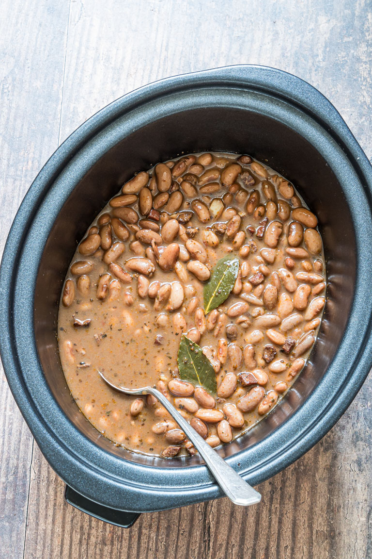 the completed crock pot pinto beans inside a slow cooker and being served with a silver spoon