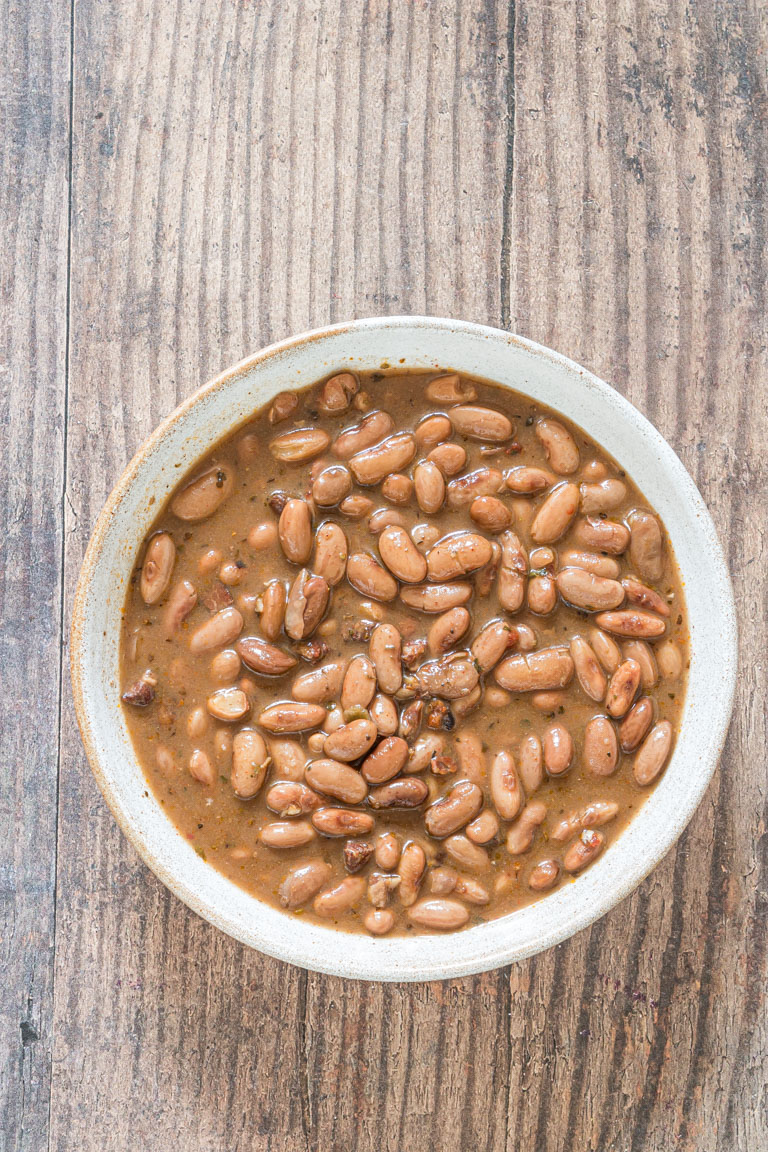 top down view of crock pot pinto beans served in a ceramic bowl