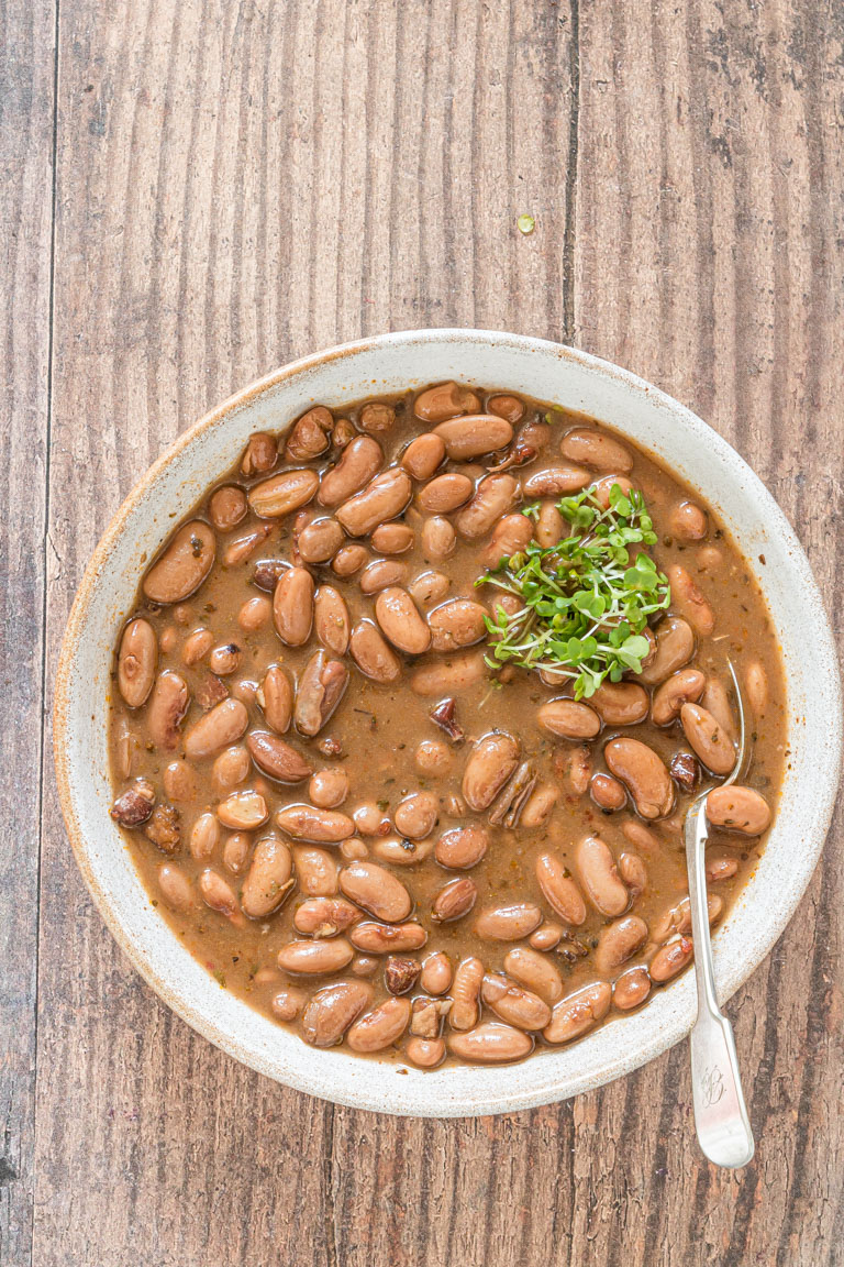 the completed slow cooker pinto beans in a bowl with a silver serving spoon and garnished with herbs