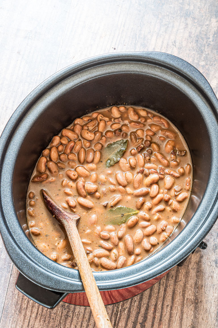 the cooked pinto beans inside a slow cooker with a wooden mixing spoon inside