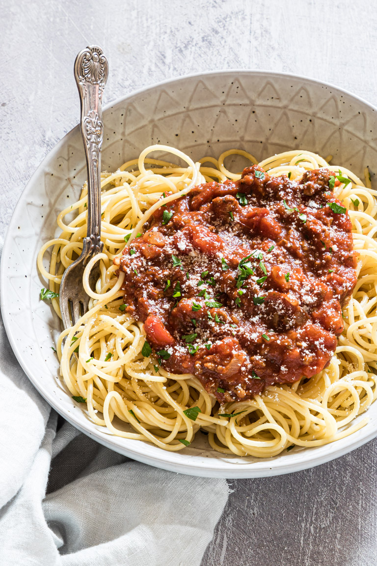 a bowl filled with pasta noodles topped with crock pot spaghetti sauce and served with a fork
