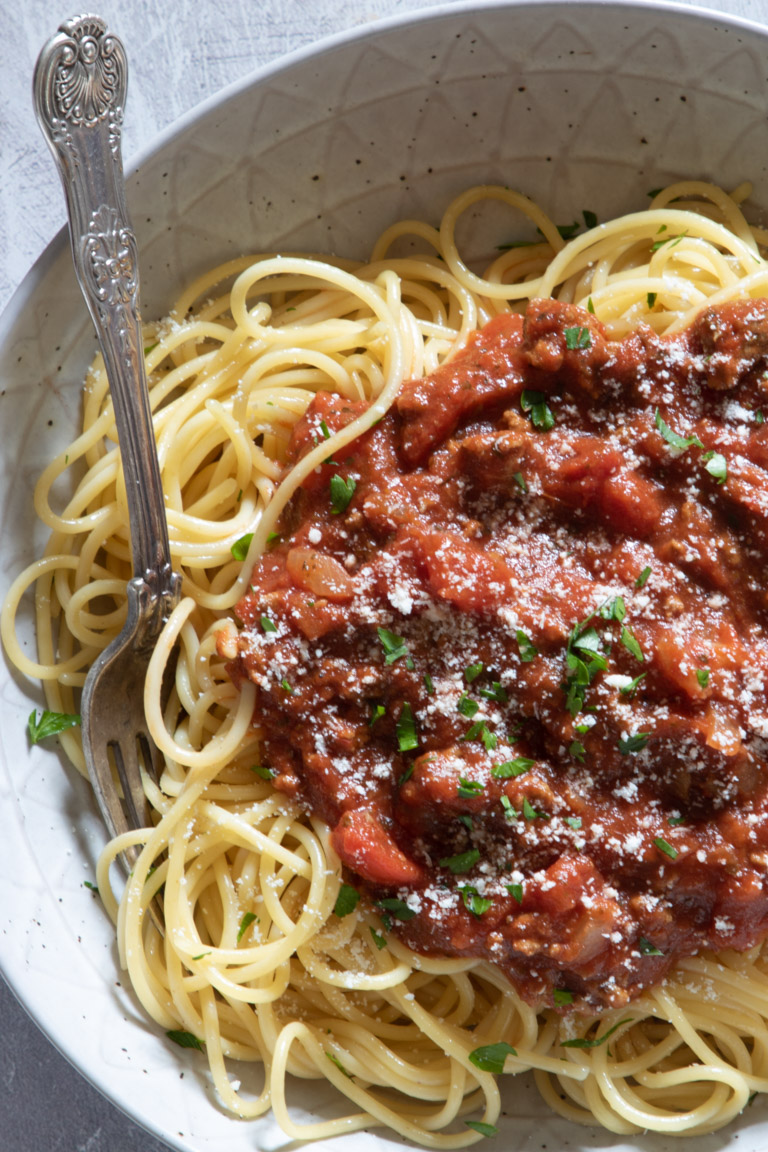close up view of spaghetti sauce served over pasta