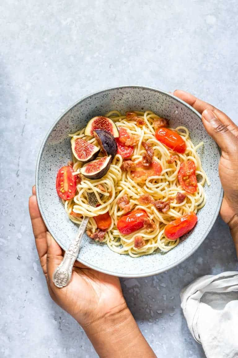 hands holding a bowl filled with a serving of garlic butter pasta with parma ham recipe