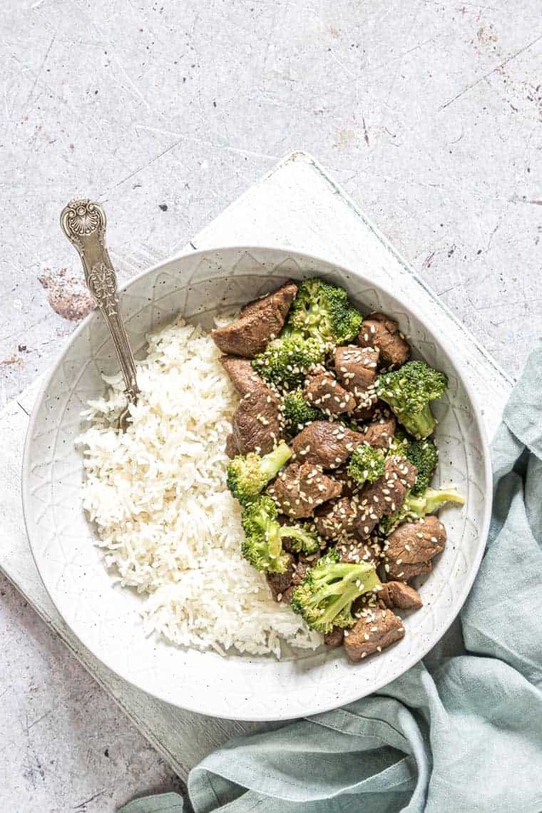bowl filled with instant pot beef and broccoli alongside a serving of white rice