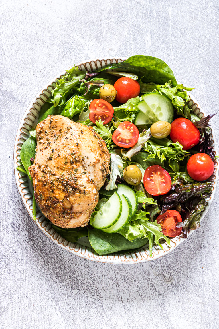 one cooked chicken breast served with a salad