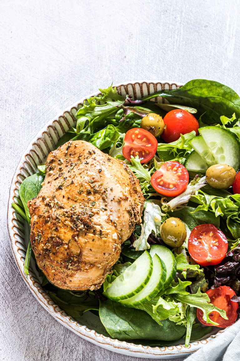 sliced chicken breast served with a green salad